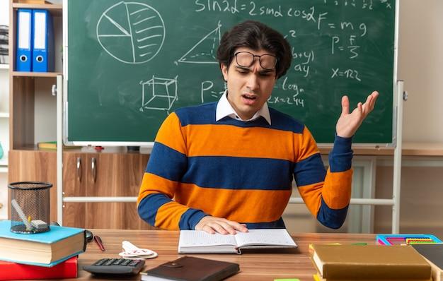 Infastidito giovane insegnante di geometria caucasica con gli occhiali sulla fronte seduto alla scrivania con materiale scolastico in classe tenendo la mano sul libro aperto leggendolo mostrando la mano vuota