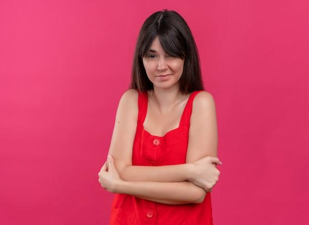 腕を組んで、コピースペースで孤立したピンクの背景にカメラを見て手で保持しているイライラする若い白人の女の子