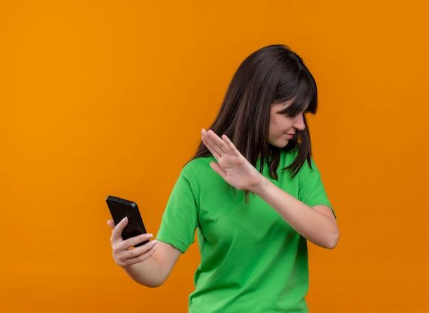 La giovane ragazza caucasica infastidita in camicia verde tiene il telefono e gesti no su fondo arancio isolato con lo spazio della copia