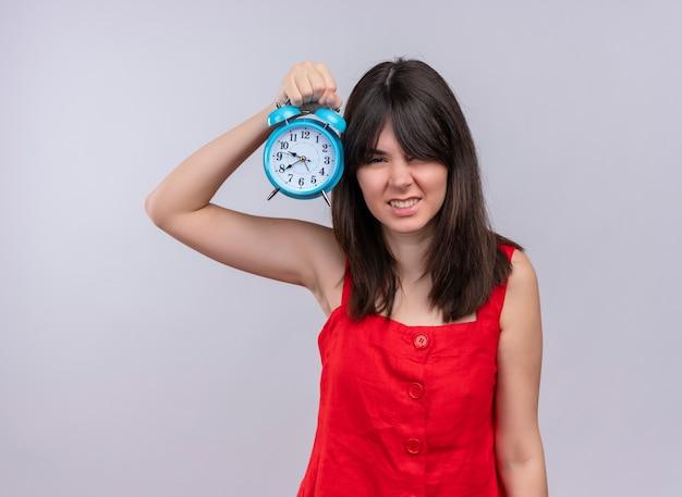 コピースペースと孤立した白い背景に手で時計を保持しているイライラする若い白人の女の子