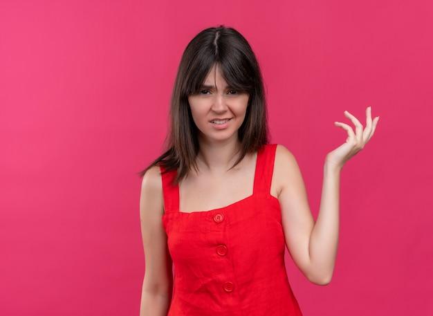 コピースペースと孤立したピンクの背景にカメラを見て空の手を保持しているイライラする若い白人の女の子