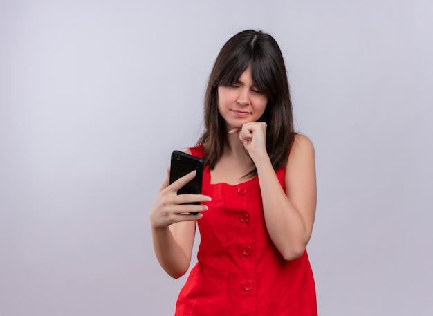 電話を保持し、孤立した白い背景の上のカメラを見ているあごに手を置いてイライラする若い白人の女の子