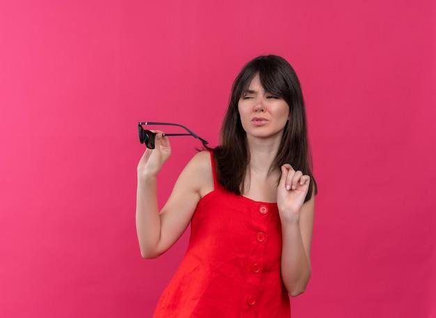サングラスを保持し、孤立したピンクの背景で横を見てイライラする若い白人の女の子