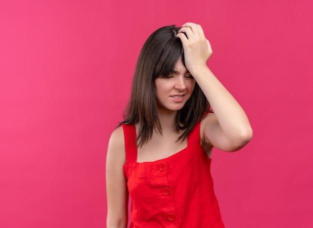 イライラする若い白人の女の子は、コピースペースで孤立したピンクの背景に頭を抱えています