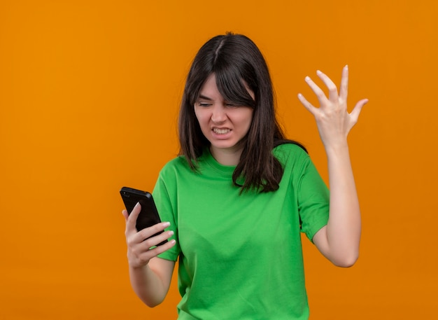 緑のシャツのイライラした若い白人の女の子は、電話を保持し、孤立したオレンジ色の背景に手を上げます。