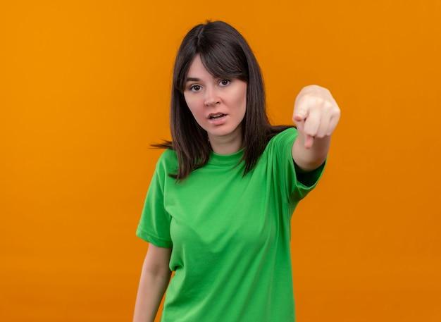 緑のシャツを着たイライラした若い白人の女の子は、孤立したオレンジ色の背景を前に指します