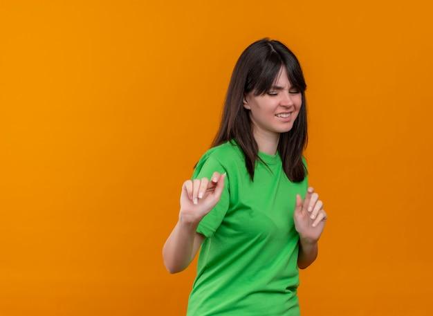 緑のシャツを着たイライラした若い白人の女の子は、コピースペースで孤立したオレンジ色の背景に何かを押すふりをします