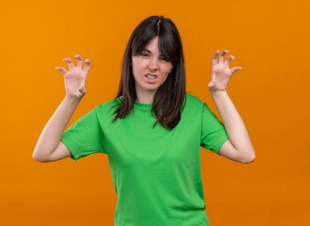 緑のシャツを着てイライラした若い白人の女の子が手を上げ、孤立したオレンジ色の背景でカメラを見る