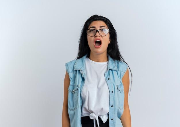 光学メガネでイライラする若い白人の女の子は、見上げる誰かに怒鳴ります