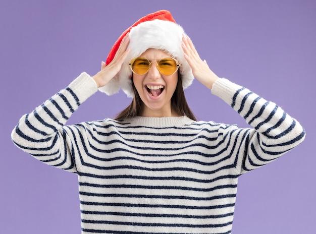 Раздраженная молодая кавказская девушка в солнцезащитных очках в шляпе санта-клауса держит голову и кричит на кого-то изолированного на фиолетовой стене с копией пространства