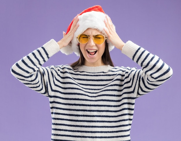 Annoyed young caucasian girl in sun glasses with santa hat holds head isolated on purple wall with copy space