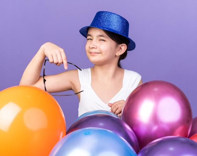 Infastidita giovane ragazza caucasica con cappello da festa blu che tiene occhiali ottici in piedi con palloncini di elio isolati sulla parete viola con spazio di copia