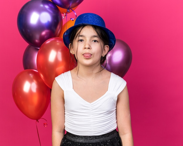 Annoyed young caucasian girl with blue party hat stucks out tongue standing in front of helium balloons isolated on pink wall with copy space