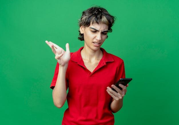 ピクシーヘアカットを保持し、コピースペースで緑の背景に隔離された空気中に手を保持している携帯電話を見ているイライラする若い白人の女の子