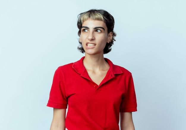 コピースペースで白い背景で隔離の側を見てピクシーヘアカットでイライラする若い白人の女の子