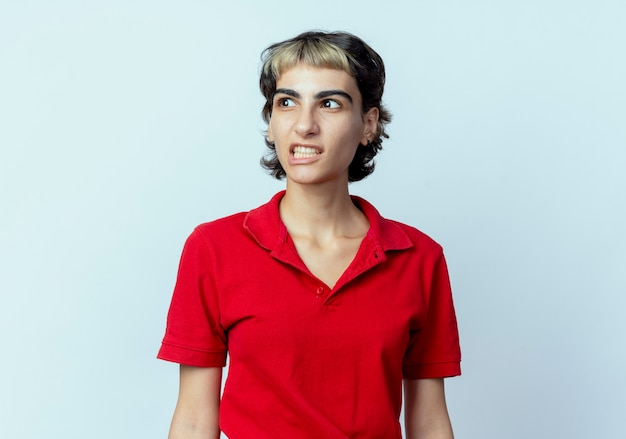 Infastidita giovane ragazza caucasica con pixie haircut guardando lato isolato su sfondo bianco con copia spazio