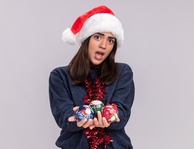 Annoyed young caucasian girl with santa hat and garland around neck holds glass ball ornaments