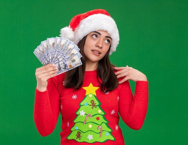 サンタの帽子をかぶったイライラする若い白人の女の子は、コピースペースで緑の背景に分離された側を見てお金を保持します