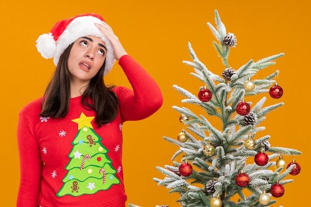 산타 모자와 짜증이 젊은 백인 여자 복사 공간이 오렌지 배경에 고립 된 크리스마스 트리 옆에 서있는 이마 롤링 눈에 손을 넣습니다