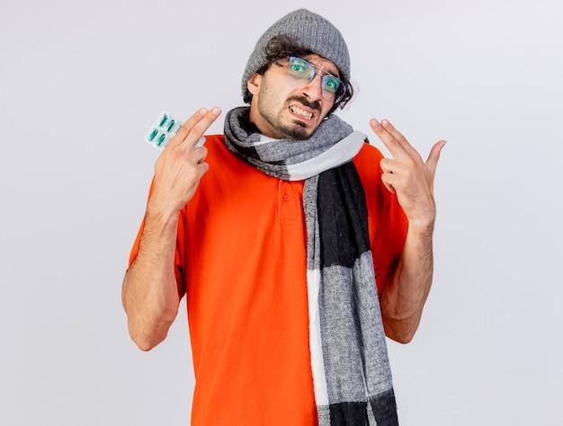 白い壁に分離されたピストルジェスチャーを行うカプセルのパックを保持している冬の帽子とスカーフで眼鏡とマスクを身に着けているイライラする若い白人の病気の男