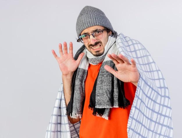 Раздраженный молодой кавказский больной в очках, зимняя шапка и шарф, завернутый в плед, смотрит в камеру, держа руки в воздухе с гипсом на носу, изолированном на белом фоне с копией пространства