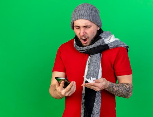 Il giovane uomo malato caucasico infastidito che indossa il cappello e la sciarpa di inverno tiene il tessuto