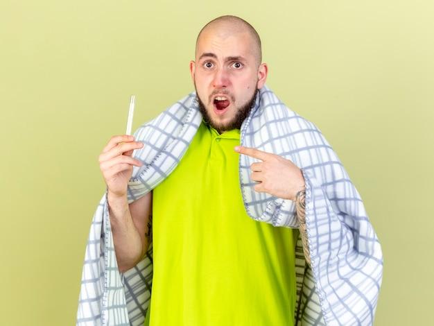 Uomo malato caucasico giovane infastidito avvolto in prese di plaid e punti al termometro isolato sulla parete verde oliva con lo spazio della copia