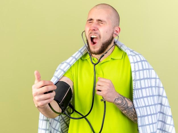 Uomo malato caucasico giovane infastidito avvolto in plaid che misura la pressione con lo sfigmomanometro