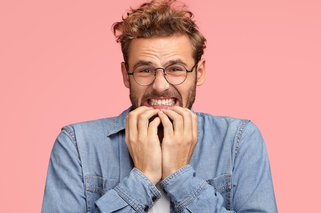Il giovane maschio caucasico infastidito stringe i denti e guarda con espressione dispiaciuta, si morde le unghie delle dita, guarda disperatamente, prova avversione, indossa una camicia di jeans, sta contro il muro rosa. oh no!