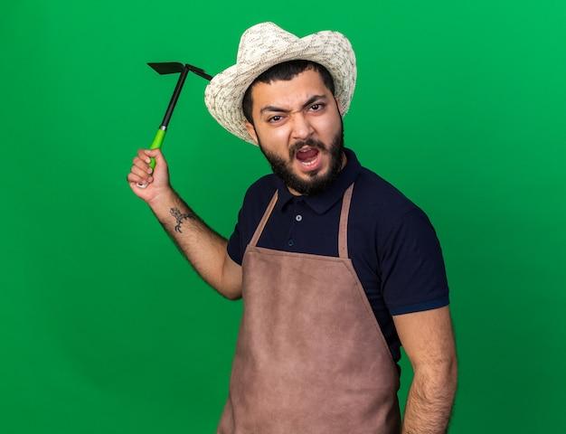 コピースペースと緑の壁に分離されたくわ熊手を保持しているガーデニング帽子をかぶってイライラする若い白人男性の庭師