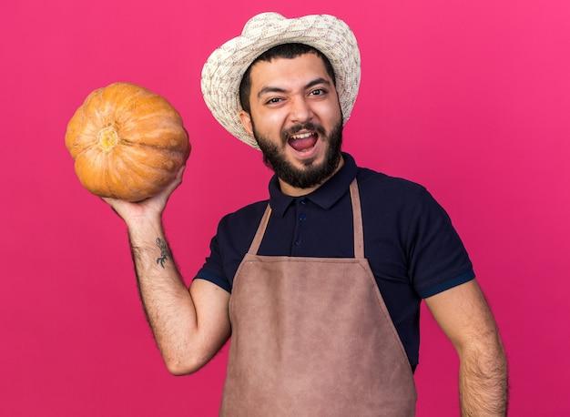 コピースペースとピンクの壁に分離されたカボチャを保持しているガーデニング帽子をかぶってイライラする若い白人男性の庭師