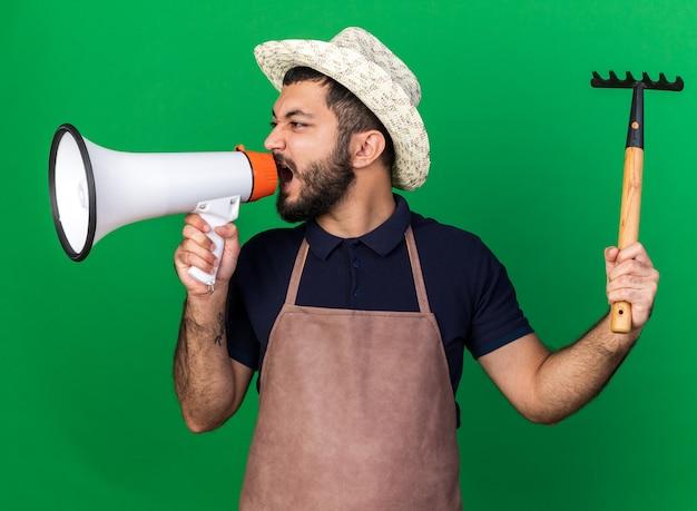 Infastidito giovane maschio caucasico giardiniere indossando giardinaggio hat holding rastrello e gridando in altoparlante guardando il lato isolato sulla parete verde con spazio di copia