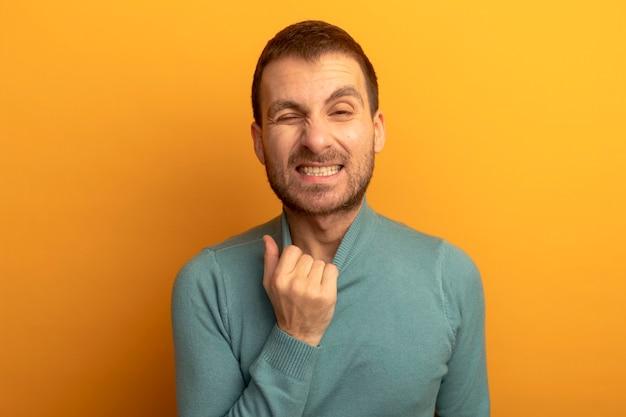 Infastidito giovane uomo caucasico tirando il collare del suo maglione a collo alto guardando la fotocamera con un occhio chiuso isolato su sfondo arancione con spazio di copia