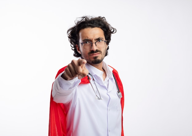 Раздраженный молодой кавказский супергерой в оптических очках, одетый в форму доктора, красный плащ и со стетоскопом на шее, указывает на камеру