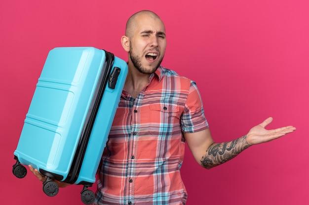 Infastidito giovane viaggiatore caucasico che tiene in mano la valigia e tiene la mano aperta isolata su sfondo rosa con spazio di copia