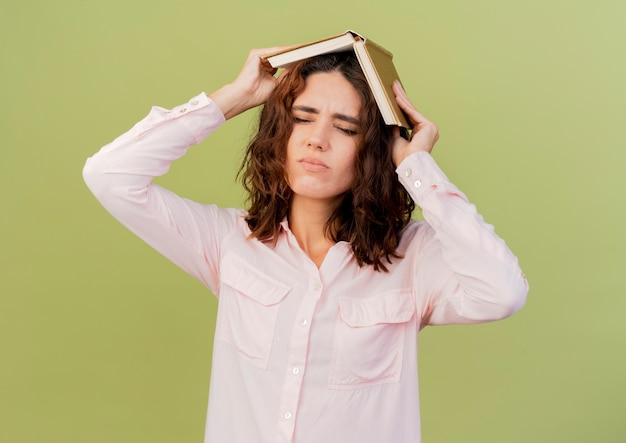 La giovane donna caucasica infastidita tiene il libro sopra la testa isolata su fondo verde con lo spazio della copia