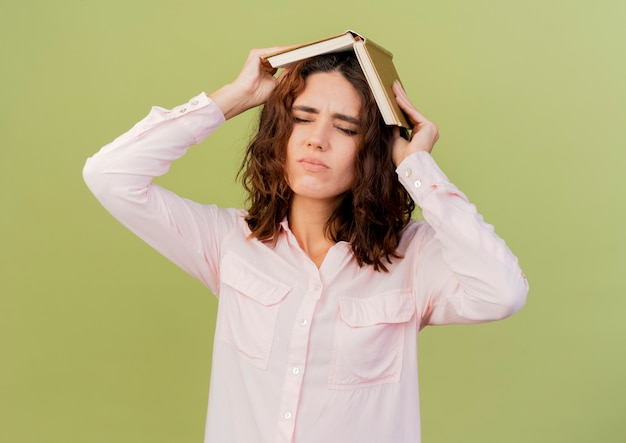 イライラする若い白人女性は、コピースペースで緑の背景に分離された頭上に本を保持します。