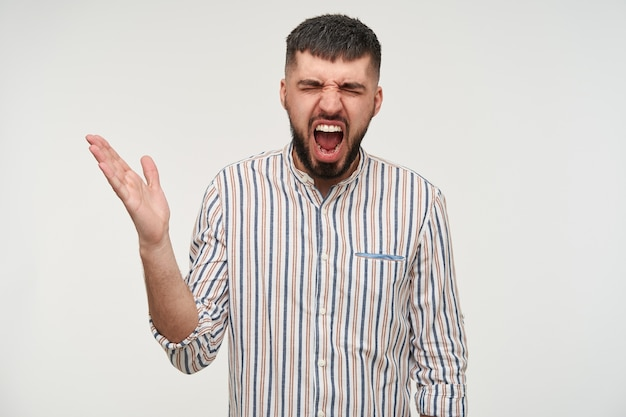Annoyed young dark haired pretty man with short haircut keeping his eyes closed while screaming and raising affectively his hand, isolated over white wall