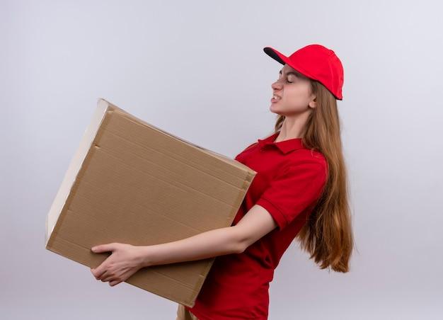 Раздраженная молодая доставщица в красной форме, держащая коробку, стоящую в профиле на изолированном белом пространстве