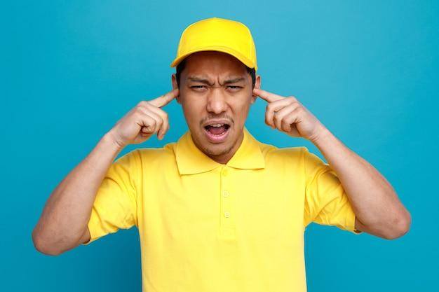 Infastidito giovane fattorino indossando l'uniforme e berretto tenendo le dita nelle orecchie