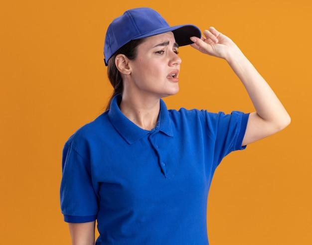 Infastidita giovane donna delle consegne in uniforme e berretto che afferra il berretto guardando il lato isolato sul muro arancione