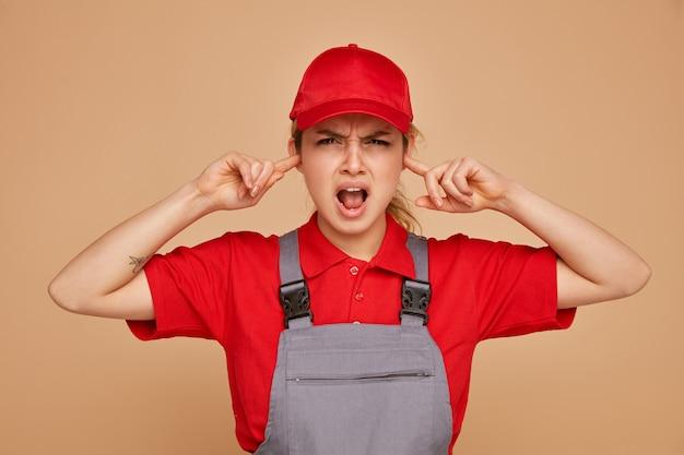 Infastidito giovane operaio edile femminile che indossa uniforme e berretto mantenendo le dita nelle orecchie
