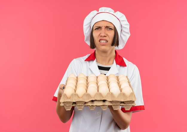 Раздраженная молодая женщина-повар в униформе шеф-повара держит коробку яиц, изолированную на розовом, с копией пространства