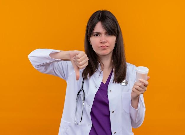 聴診器と医療ローブでイライラする若い女性医師は、孤立したオレンジ色の背景に薬のカップと親指を保持します