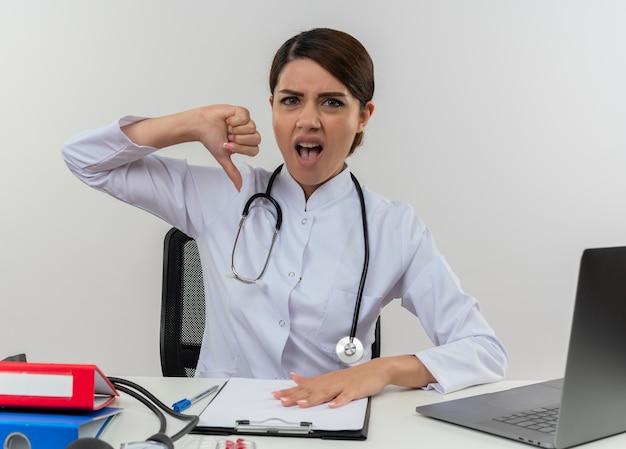 Раздраженная молодая женщина-врач в медицинском халате и стетоскопе сидит за столом с медицинскими инструментами и ноутбуком, показывая большой палец вниз изолированно на белой стене