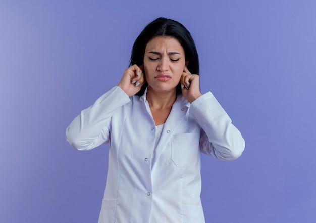 닫힌 눈으로 귀에 손을 넣어 의료 가운을 입고 짜증이 젊은 여성 의사