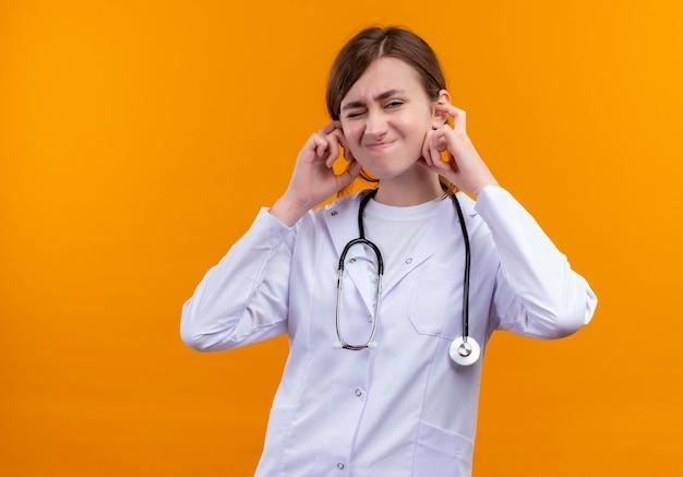 Infastidito giovane medico femminile che indossa abito medico e stetoscopio mettendo le mani sulle orecchie sullo spazio arancione isolato con lo spazio della copia