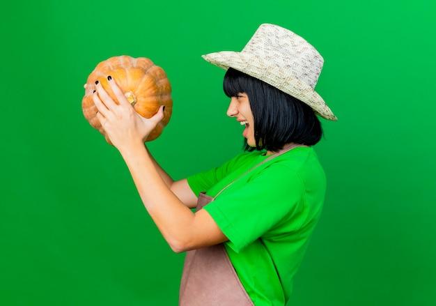 Раздраженная молодая женщина-садовник в униформе в садовой шляпе стоит боком, держа и глядя на тыкву