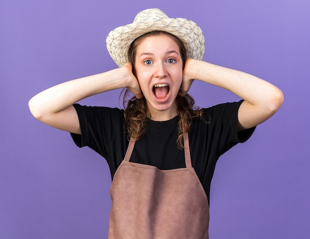 Annoyed young female gardener wearing gardening hat covered ears with hands isolated on blue wall
