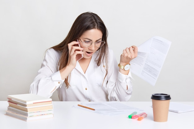 Раздраженный молодой фрилансер пытается понять информацию в газетах, имеет телефонный разговор, сердито объясняет, как сделать бизнес-проект, носит очки белую рубашку, изолированные на белом
